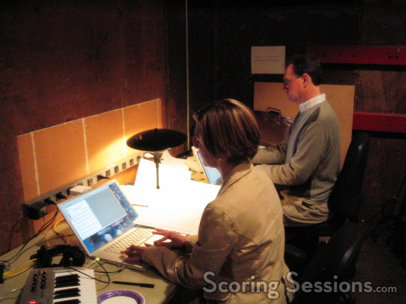 Jennifer Hammond and Marshall Bowen copy music parts for the orchestra