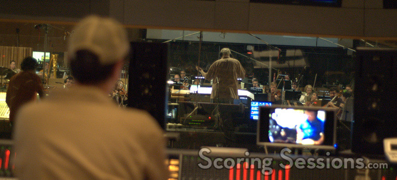 Composer Michael Giacchino watches from the booth as Tim Simonec conducts the orchestra