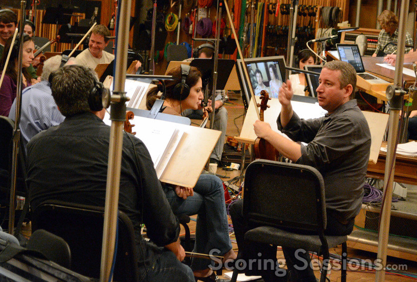 Concertmaster Mark Robertson gives notes to the strings