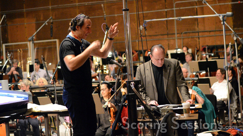 Composer and conductor Alexandre Desplat talks to the booth while orchestrator Conrad Pope reviews the score