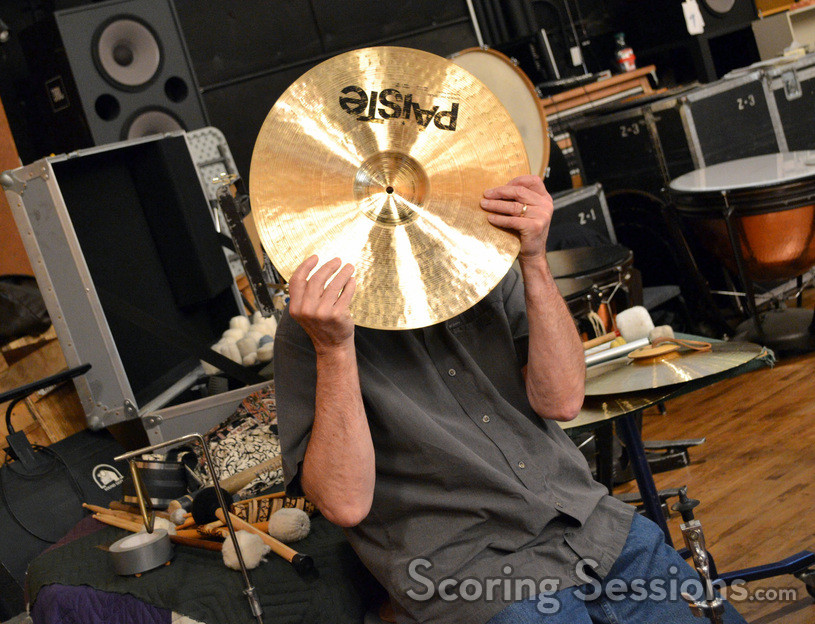 A percussionist plays coy behind a cymbal