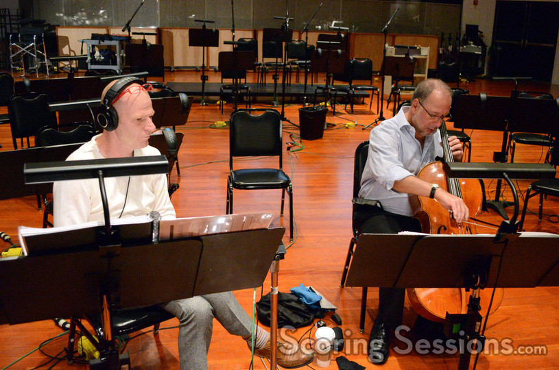 Composer Tom Holkenborg listens as Steve Erdody performs a cello solo