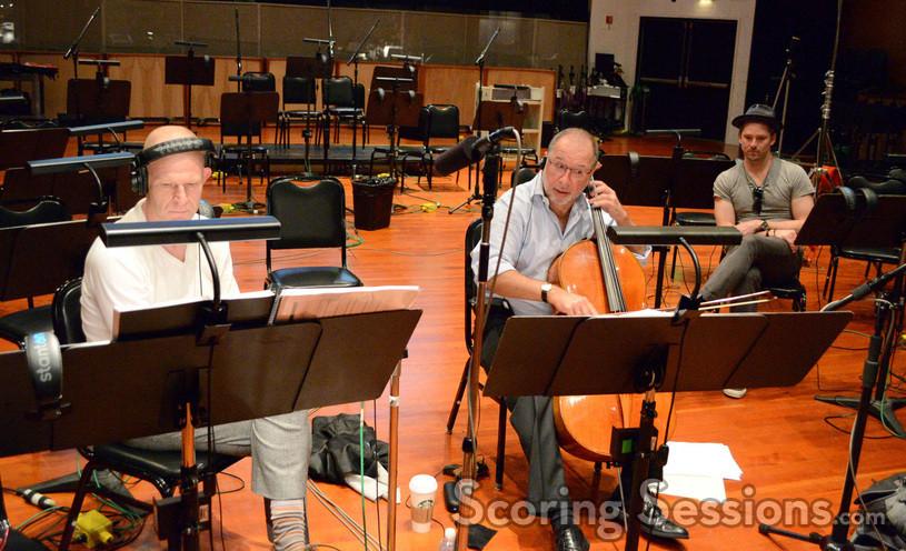 Composer Tom Holkenborg and director Scott Cooper (right rear) listen while solo cellist Steve Erdody performs