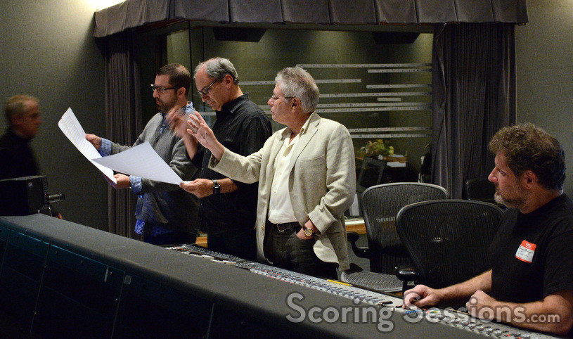 Composers Christopher Lennertz (left) and Alan Menken (standing, right) go over the score with conductor Michael Kosarin (standing, middle) as scoring mixer Frank Wolf watches