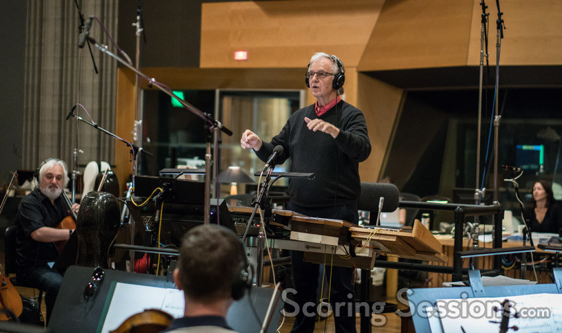 Composer Bruce Broughton checks with the playback as he conducts