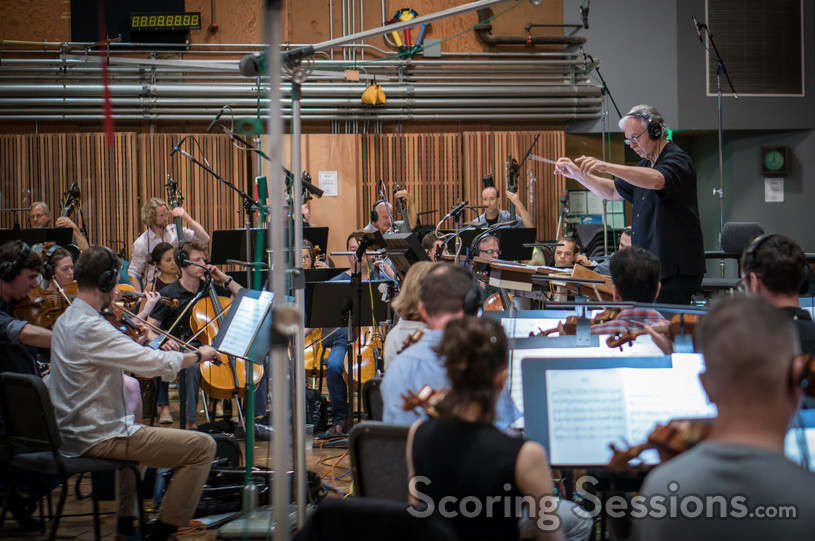 Composer/conductor Bruce Broughton records a cue with the orchestra