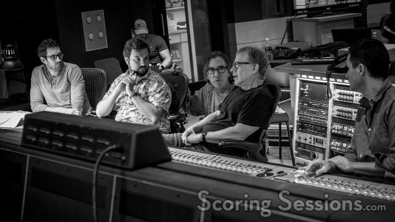 Orchestrator Philip Klein, additional music composer David Buckley, and scoring mixer Noah Snyder (right) listen as composer Danny Elfman talks with music editor Bill Abbott (kneeling)