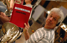 French horn player Joe Meyer holds up the last score