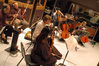The string section waits between cues