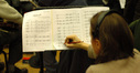 A musician makes a note on a score sheet