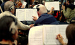 Musicians note a change on their score sheets