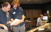 Conductor/orchestrator Jason Poss and composer Jesper Kyd examine a score sheet, while John Kurlander adjusts the sound