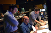 Composer John Paesano, orchestrator Randy Kerber and composer assistant Braden Kimball examine a cue