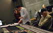 Score coordinator Andrea Datzman and composer Michael Giacchino discuss a cue as guitarist George Doering (rear) and scoring mixer Dan Wallin wait to record