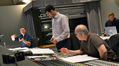 Orchestrator Stephen Coleman discusses a cue with composer Ramin Djawadi and scoring mixer Dennis Sands