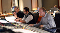 Orchestrator Andrew Kinney, composer Christopher Lennertz, and scoring mixer Jeff Vaughn listen to playback