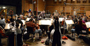 Composer and conductor Joel McNeely and the orchestra prepare to record the next cue