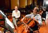 Composer Tom Holkenborg listens as Steve Erdody demonstrates his take on a cello solo