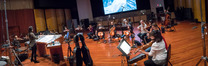 Composer/conductor Sherri Chung and the orchestra record a cue