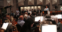 Composer Michael Giacchino addresses the orchestra with the music team in tow