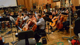 The orchestra listens to playback