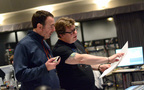 Composer John Paesano and scoring mixer Alan Meyerson go over a cue together