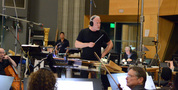 Composer/conductor John Debney listens to feedback from the booth