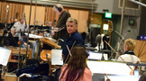 Concertmaster Bruce Dukov talks with the violin section