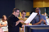 Composer Chris Lennertz and supervising music editor Todd Bozung look over a cue as director Tim Story watches playback
