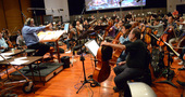 Conductor/orchestrator Nicholas Dodd shows the cellos exactly what he wants