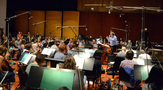 Conductor/orchestrator Nicholas Dodd performs a cue with the orchestra