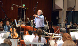 Conductor/orchestrator Nicholas Dodd gives feedback to the orchestra
