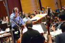 Conductor/orchestrator Nicholas Dodd gives notes to the cello section