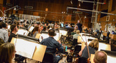 Composer/conductor Brian Tyler gives feedback to the violin section