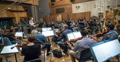 Composer/conductor John Powell and the orchestra