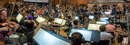 The view from the violin section as composer John Powell conducts the orchestra during the <i>Ferdinand</i> sessions