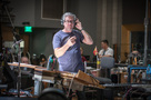 Composer/conductor John Powell gives feedback to the violins