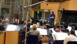Conductor Mark Graham listens for instructions from the booth