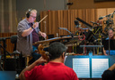 Composer Joel McNeely conducts the orchestra