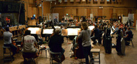 Conductor/orchestrator Tim Davies and the orchestra perform a cue from <i>Rings</i>