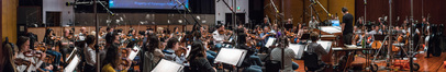 The orchestra records a cue with conductor James Sale