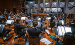 Conductor Nick Glennie-Smith records a cue from <i>Aquaman</i> with the orchestra