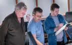 Composer Rupert Gregson-Williams (center) reviews a cue with conductor Nick Glennie-Smith (left) and technical score engineer Forest Christenson