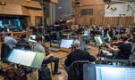 Conductor/orchestrator Tim Williams and the orchestra record a cue