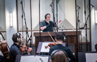 Conductor Lucas Richman and the orchestra perform
