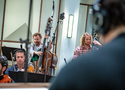 A peak at the orchestra over the shoulder of conductor Lucas Richman