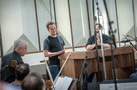 Composer Nathan Barr (center), conductor Lucas Richman (right), and orchestra contractor David Low (left) address the orchestra