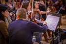 Concertmaster Mark Robertson makes a notation on the music
