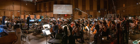 The orchestra records a cue with composer/conductor Joseph Trapanese