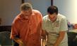 Conductor Tim Simonec and composer Chris Tilton examine a cue